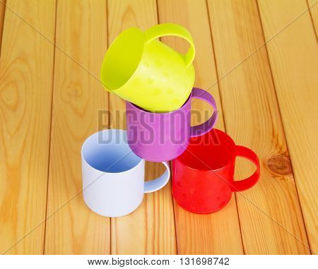 Four different color plastic mugs on the background of light wood.