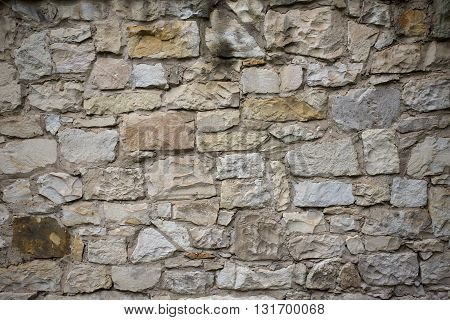 Stone old wall with heather. Stone wall texture. Old rock blocks in old medieval brick. Exterior historical country situation with fencing. Village rural foundation background.
