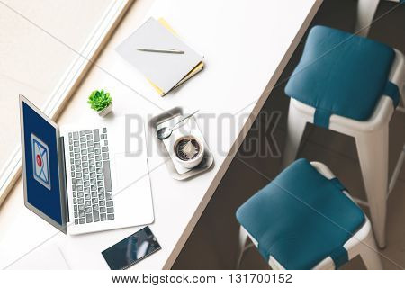 Top view of laptop and cup of coffee on the desk near a window