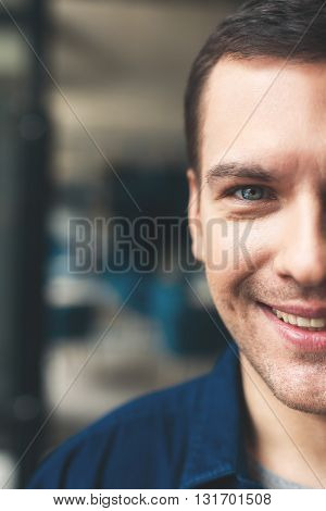 Close up of half of male face. Man is standing and smiling. He is looking at camera with happiness