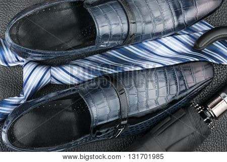 Classic blue shoes tie umbrella on the black leather can be used as background