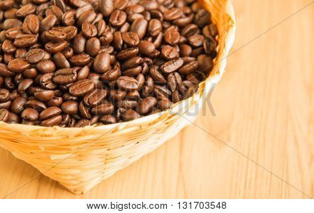Coffee beans in bamboo panier on the wood background