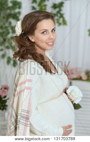fashion photo of beautiful pregnant woman with long dark hair posing in studio interior with white rose