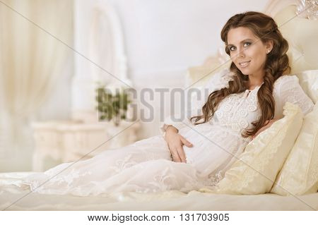 fashion photo of beautiful pregnant woman with long dark hair posing in cozy interior