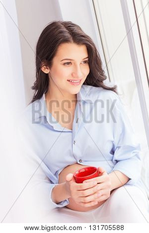Pretty young expectant mother is sitting and resting on windowsill. She is holding a cup of hot tea. The woman is dreaming and smiling
