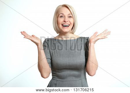 Woman looking surprised. Friendly smiling middle-aged woman isolated on white background