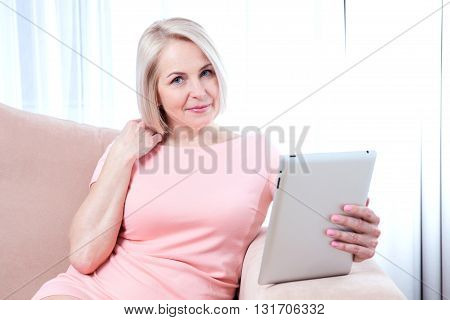 Smiling beautiful middle aged woman sitting on couch with tablet considering new idea.