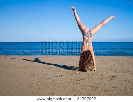 Woman Jumping On The Beach Enjoying Summer Vacation