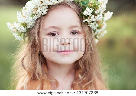 Cute kid girl 4-5 year old with flowers in hairstyle outdoors. Looking at camera. Childhood.