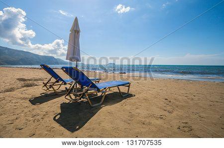 Empty Lounge Chairs With Sun Umbrella On Sandy Beach