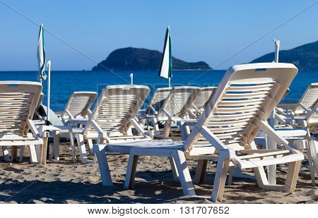 Empty Lounge Chairs On Sandy Beach Before Summer Season