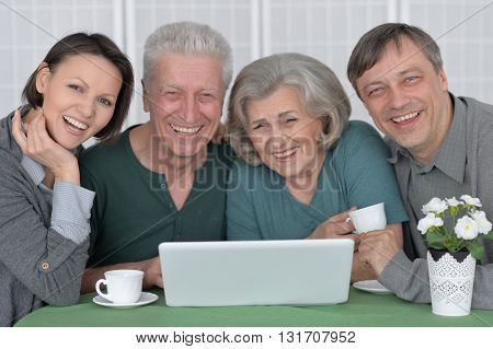 Happy smiling family portrait with a laptop