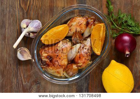 Baked in the oven chicken with orange garlic and onion, top view
