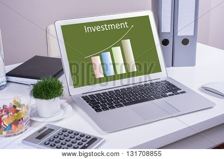 Computer with positive investment chart on desk