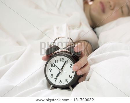 Single women sleep on white bed and rise hand to turn off alarm clock don't want to wake up in the morning (Soft light color tone effect)