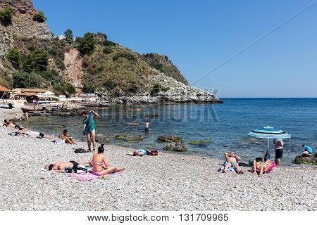 TAORMINA ITALY - MAY 21: Tourists relaxing at the beach of Taormina on May 21 2016 at the island Sicily Italy