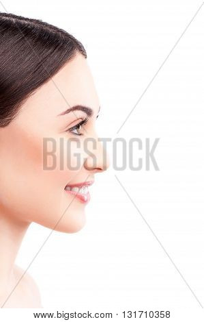 Attractive girl with healthy skin is standing in profile. She is smiling. Isolated and copy space in right side