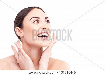 Attractive healthy girl is satisfied with her skin. She is raising arms to face. The lady is standing and smiling with happiness. Isolated and copy space in right side