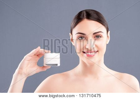 Portrait of pretty healthy girl showing a tank of cream. She is standing and smiling. The lady is looking at camera with satisfaction. Isolated on grey background