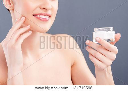 Cheerful young woman is treating her skin with cream. She is standing and holding a tank. The lady is smiling with satisfaction. Isolated