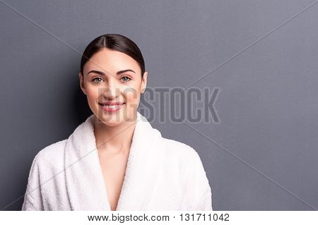 Waist up portrait of beautiful young woman standing in a white bathrobe. She is looking at camera and smiling. Isolated and copy space in right side