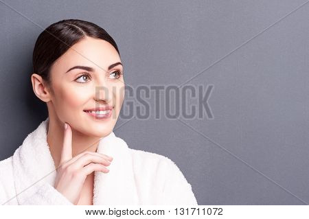 Portrait of attractive woman dreaming and smiling. She is standing in white bathrobe. The lady is touching finger to her chin pensively. Isolated and copy space in right side