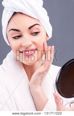 Portrait of pretty young woman holding a mirror and smiling. She is touching her face and looking at her reflection with satisfaction. The lady is wearing bathrobe and towel. Isolated