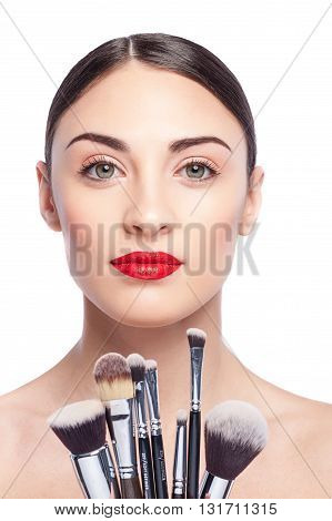 Portrait of attractive young woman holding a set of make-up brushes. She is standing and looking at camera with confidence. Her lips are red. Isolated