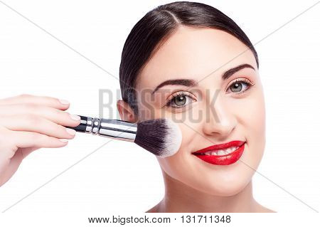 Close up of hand of beautician applying powder on female face. Pretty young woman is looking at camera and smiling. Isolated