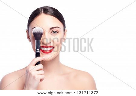 Portrait of pretty girl covering her eye with a powder brush. She is looking at camera and smiling. The lady is standing with naked shoulders. Isolated and copy space in right side