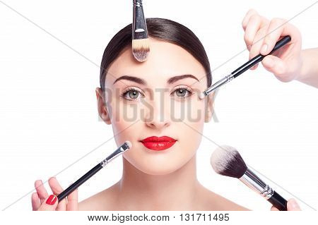 Portrait of attractive young woman getting facial make-up by different brushes. She is looking at camera with confidence. The hand of beautician is applying eyeshadows. Isolated