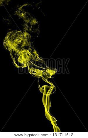 Abstract yellow smoke on black background from the incense sticks