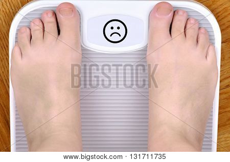 Barefoot person standing on the weight scale. The scale shows sad smiley face