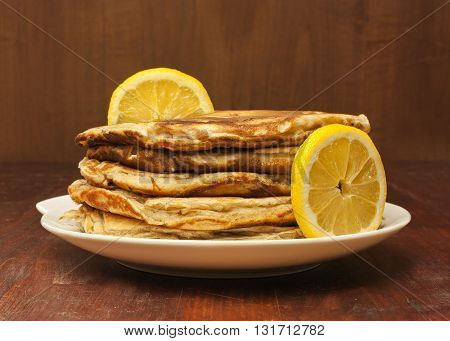 A photo of a stack of freshly baked homemade pancakes decorated with lemon slices on a dark brown wooden background with copyspace