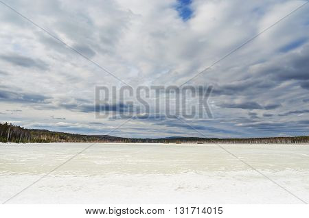 Spring landscape with unusual sky and frozen pond
