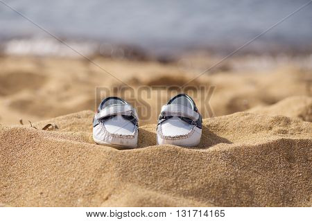 Baby shoes on light background in sandy beach, conceptual photo of summer holidays