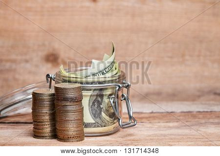 Glass jar with dollar banknotes and piles of coins