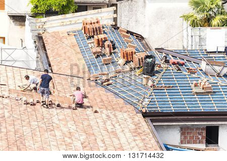 Udine , Italy - May 2 2016 :  Masons to work on the roof for laying tiles