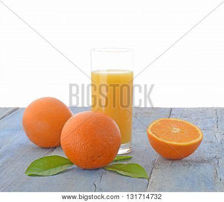 Oranges and glass of orange juice on wooden table