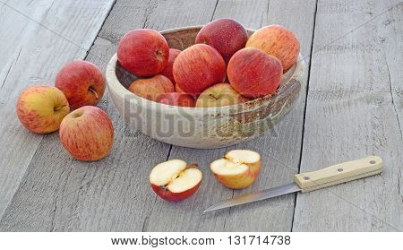 Apple in vase with cut apples  on wooden table
