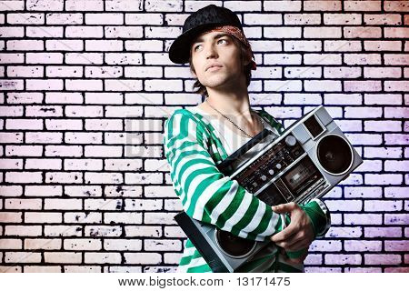 Trendy young man posing  against a brick wall with tape recorder.