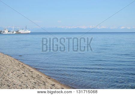 Beach in Listvyanka village. Smooth calm surface of Lake Baikal in spring