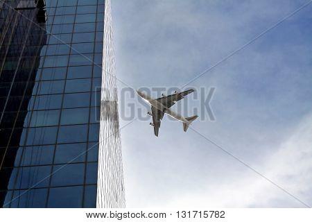 TEL AVIV ISRAEL - FEBRUAR 12 2010: Passenger plane flying over the city near the skyscraper