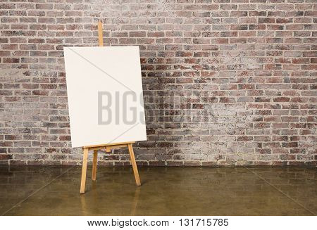 Easel with canvas on a grunge brick wall background
