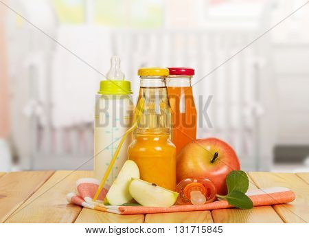 Bottles with milk and juice, fruit puree Bank, apples, spoon and soother on the background of the kitchen.