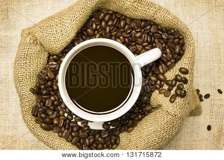 Top view a cup of hot coffee sitting in a bag of fresh coffee beans on burlap background