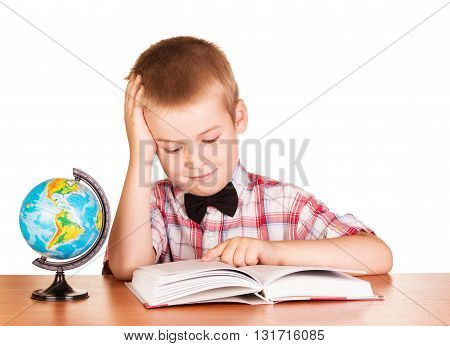 Cute schoolboy reading a book, the globe on the table isolated on white background.