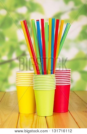 Disposable paper cups and straws on abstract green background.