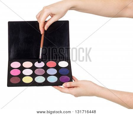 The female hands eyeshadow palette and cosmetic brush isolated on white background.