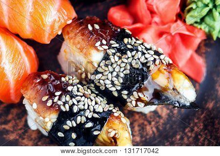 Sushi Set sashimi and sushi rolls served on dark plate. Image of Japanese food on dark background.